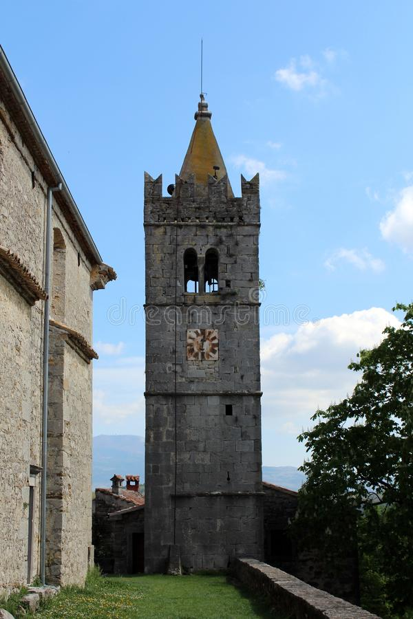 Stone bell tower with metal clock. Large stone bell tower with yellow top and rusted old metal clock in the middle royalty free stock photos