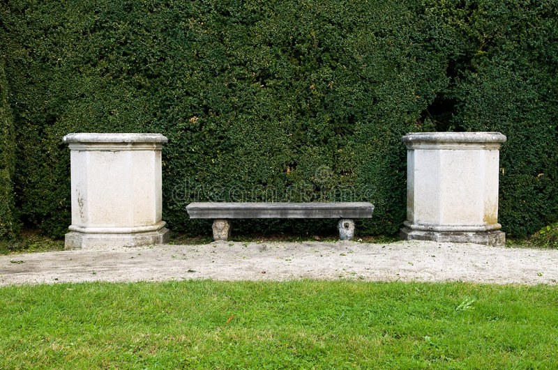 Stone bench. In the garden stock images