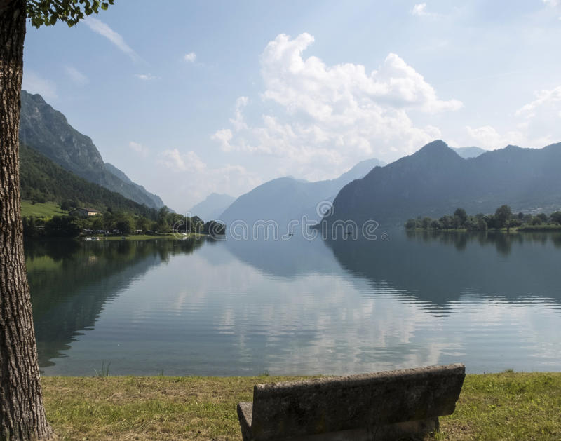 Stone bench and panoramic view with mountains reflected on water stock photography