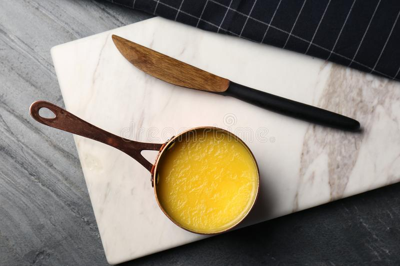 Stone board with saucepan of clarified butter and knife on table. Flat lay stock image