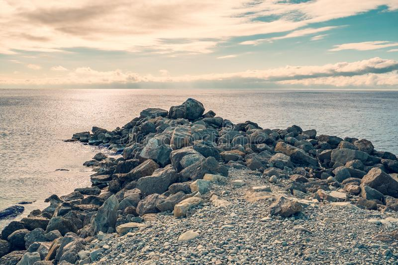 Stone breakwater at sea coast as ocean and travel background royalty free stock images