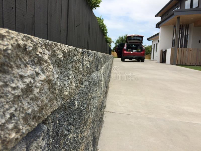Moving new home. Move concept. Stone brick wall close up front yard, car opening back door, and entrance of the house. royalty free stock photography