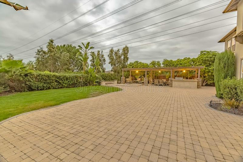 Stone brick driveway and patio with fire pit and dining area under a pavilion stock photography