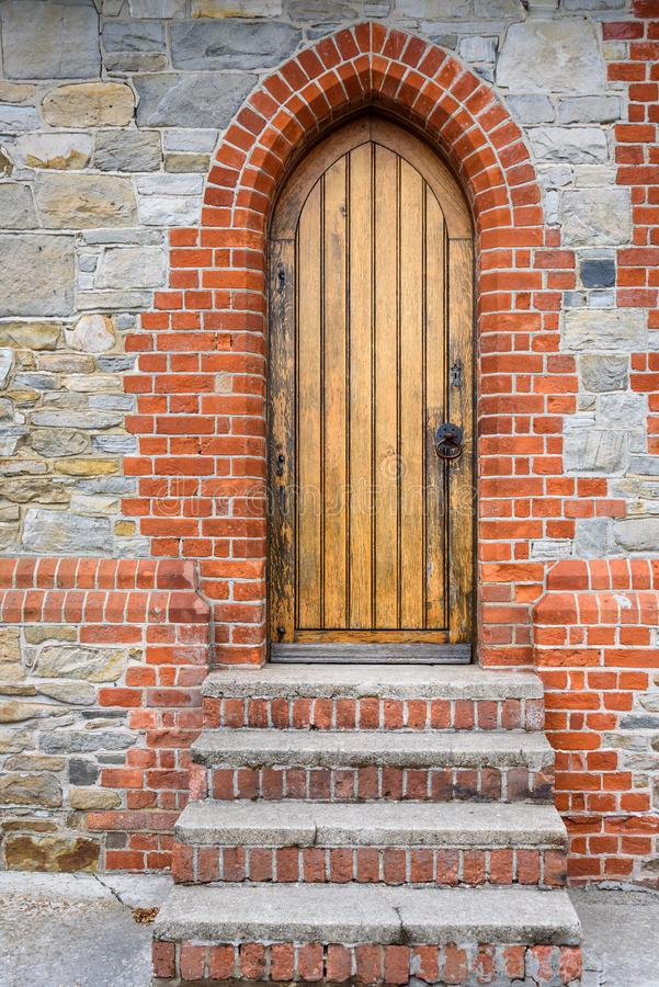 Stone and brick exterior detail of Christ Church Cathedral, brick and concrete stairs leading up to a wooden side door royalty free stock image