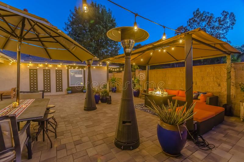 Stone brick patio of a home illuminated with string lights and lamp posts stock images