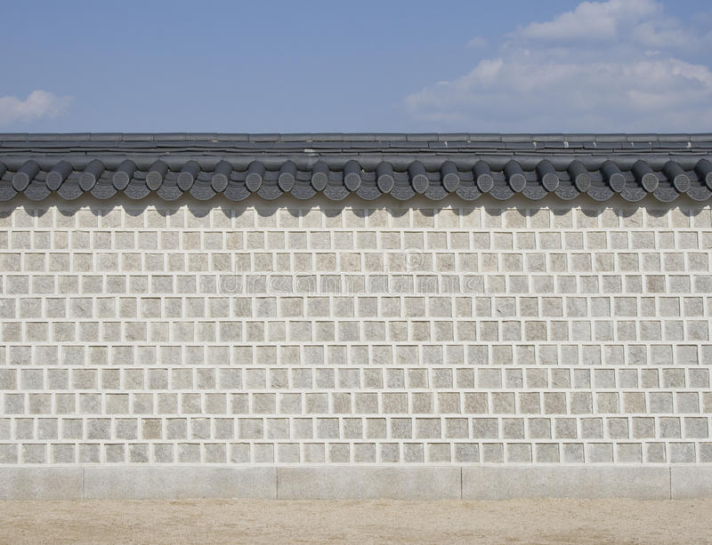 Stone brick wall. Detail of cemented regular shaped stone brick wall with oriental roof tiles.Gyeonbokgung, National Palace Museum, Seoul, Korea royalty free stock image