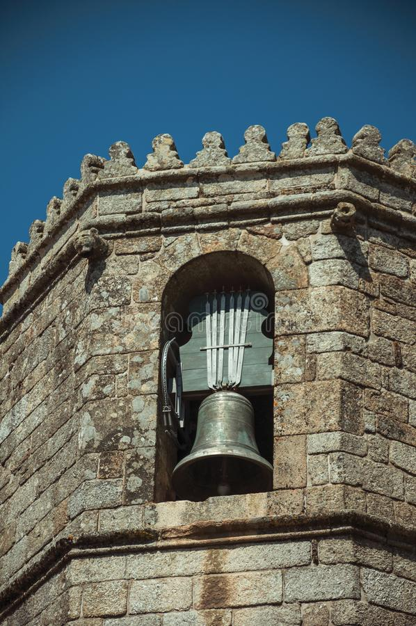 Stone brick wall and bronze bell on steeple at the Cathedral of Guarda royalty free stock image