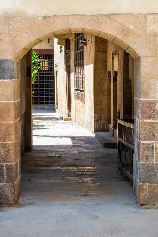 Stone bricks wall with aged vaulted passage, Old Cairo, Egypt. Stone bricks wall with aged vaulted passage, Beit El Sehemy, Medieval Cairo, Egypt royalty free stock photos