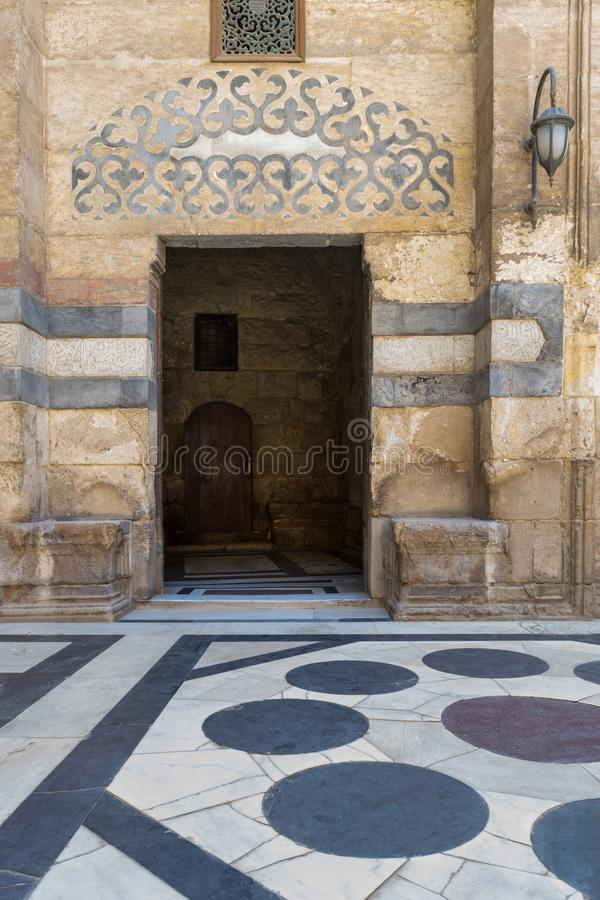 Stone bricks wall and opened door leading to passage at the courtyard of Sultan Barquq Mosque, Cairo. Stone bricks wall and opened door leading to passage at the stock photography