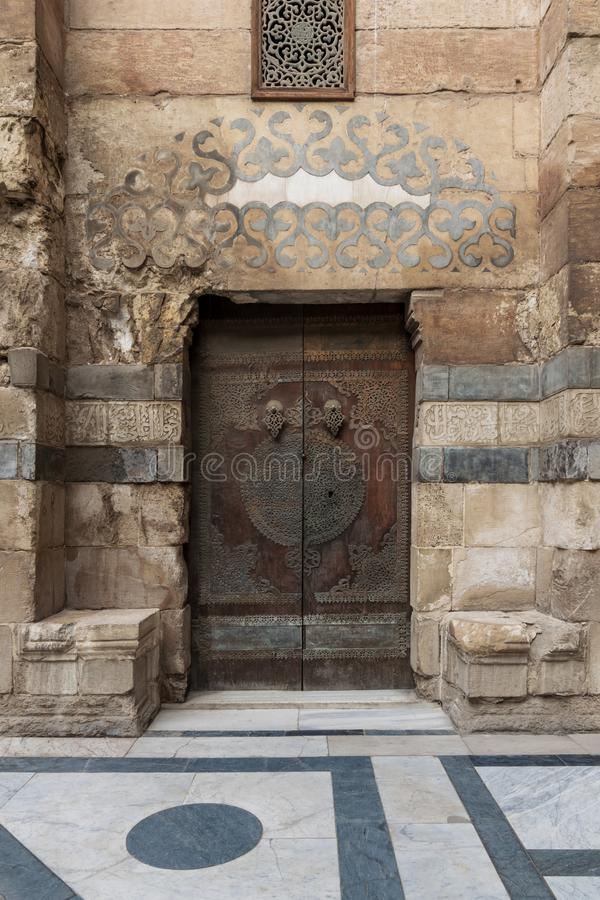 Stone bricks wall and wooden decorated copper plated door at Sultan Barquq mosque, Cairo, Egypt. Stone bricks wall and wooden decorated copper plated door stock photos