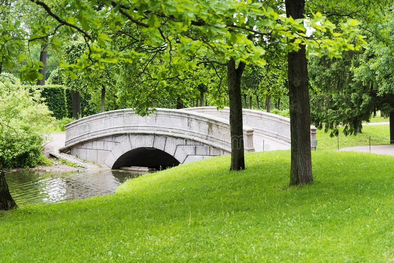 Stone bridge with an arch across the stream in the summer Park. Stone bridge with arch across the stream in the summer Park on a Sunny day stock photo