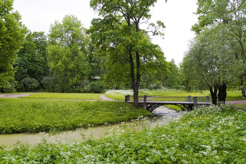 Stone bridge with an arch across the stream in the summer Park. Stone bridge with arch across the stream in the summer Park on a Sunny day royalty free stock images