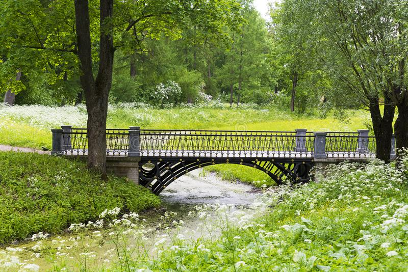 Stone bridge with an arch across the stream in the summer Park. Stone bridge with arch across the stream in the summer Park on a Sunny day stock photos