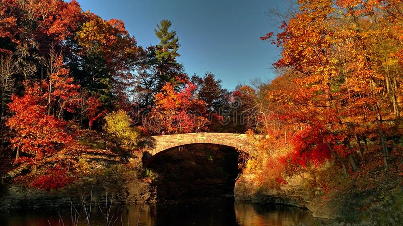 Stone Bridge Crossing River in Autumn Near Cornell University, Ithaca NY. Autumnal, colors, red, orange, blue, sky, copyspace, pond, waterway, trees, forest royalty free stock photos