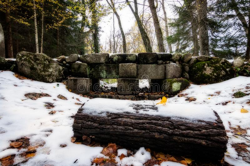 Stone bridge crossing the snow in the woods. royalty free stock photography