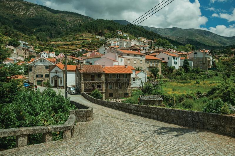 Stone bridge and houses going up on the hilly landscape royalty free stock photos