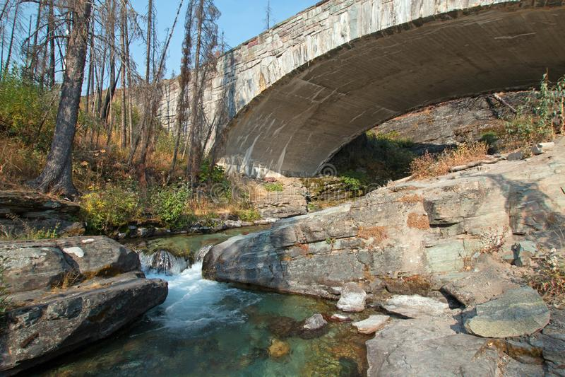 STONE BRIDGE OVER BARING CREEK ON THE GOING TO THE SUN ROAD IN GLACIER NATIONAL PARK IN MONTANA USA. STONE BRIDGE OVER BARING CREEK ON THE GOING TO THE SUN ROAD stock photography