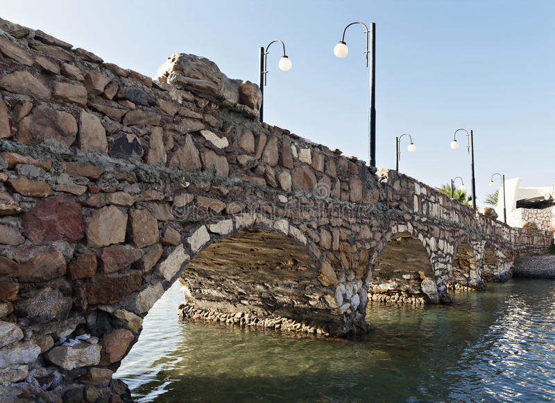 Stone bridge over a close-up perspective river stock images