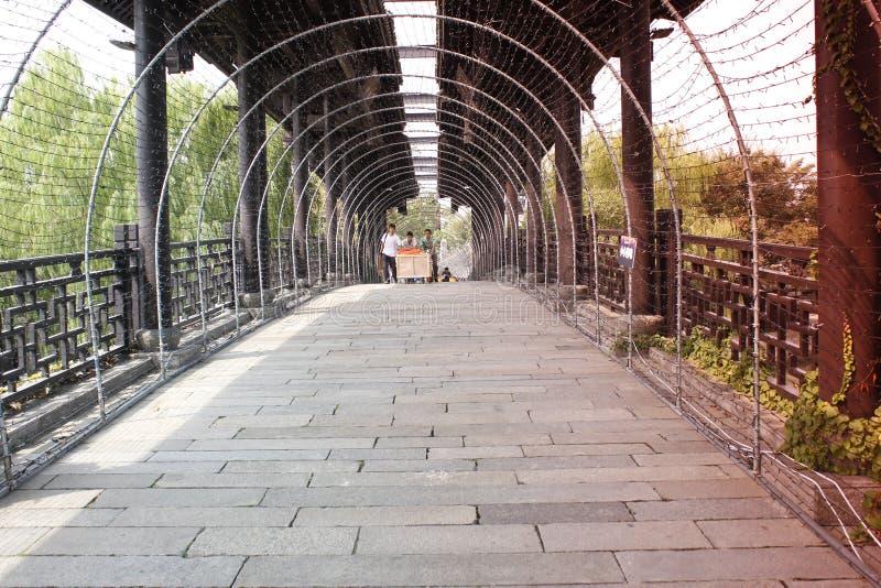 A stone bridge with rain roof and LED light curve crossing a small river. A stone bridge with rain roof and LED light curve crossing the river royalty free stock image