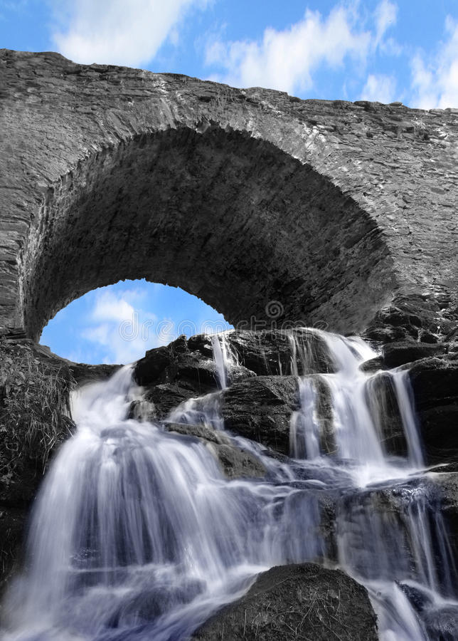 Arched stone bridge with a waterfall and blue sky. Impressive old building with beautiful detail of running water stock photo