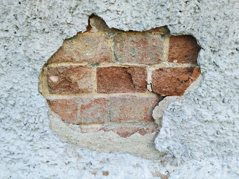 A hole in the wall. Chipped piece of plaster. Under the rough surface is a brick wall. The stone is broken and uneven. royalty free stock photo