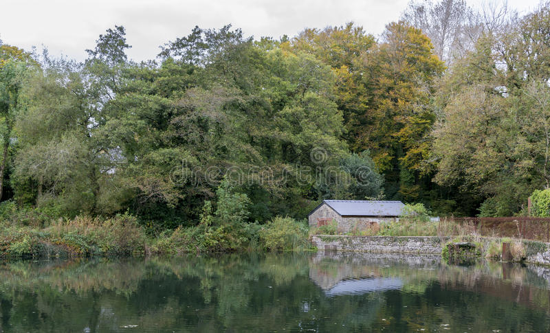 Stone building, on a lake shore in the forest. In the autumn, with the building and the trees reflecting in the lake stock photography