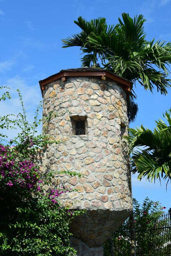 Watch Tower At Harvest Caye Island. Stone building watch tower at Harvest Caye Island surrounded by palm trees and flowers stock photo