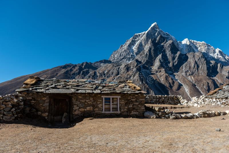 Stone built cabin with a beautiful view of the snowcapped mountain. A stone built cabin with a beautiful view of the snowcapped mountain in the background on a royalty free stock images