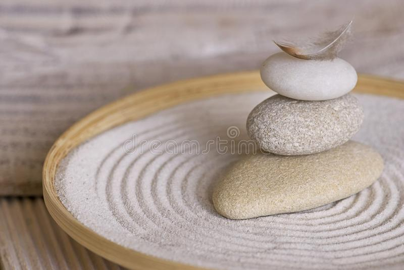 Stone Cairn With Feather In Bamboo Bowl. Balanced stack of smooth pebble with little feather on top in a bamboo bowl with raked sand in the style of a Japanese stock image
