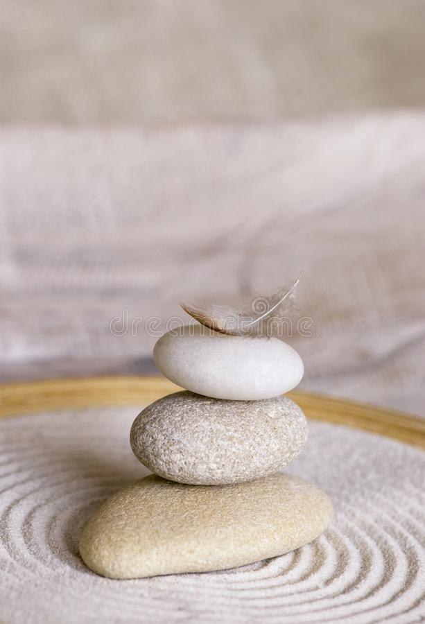 Stone Cairn With Feather In Bamboo Bowl. Balanced stack of smooth pebble with little feather on top in a bamboo bowl with raked sand in the style of a Japanese royalty free stock photos