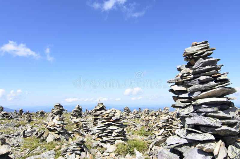 Stone cairn with grass and blue sky background stock image