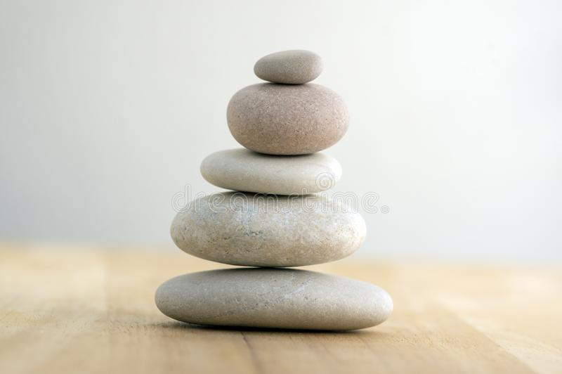 Stone cairn on striped grey white background, five stones tower, simple poise stones, simplicity harmony and balance, rock zen royalty free stock photography
