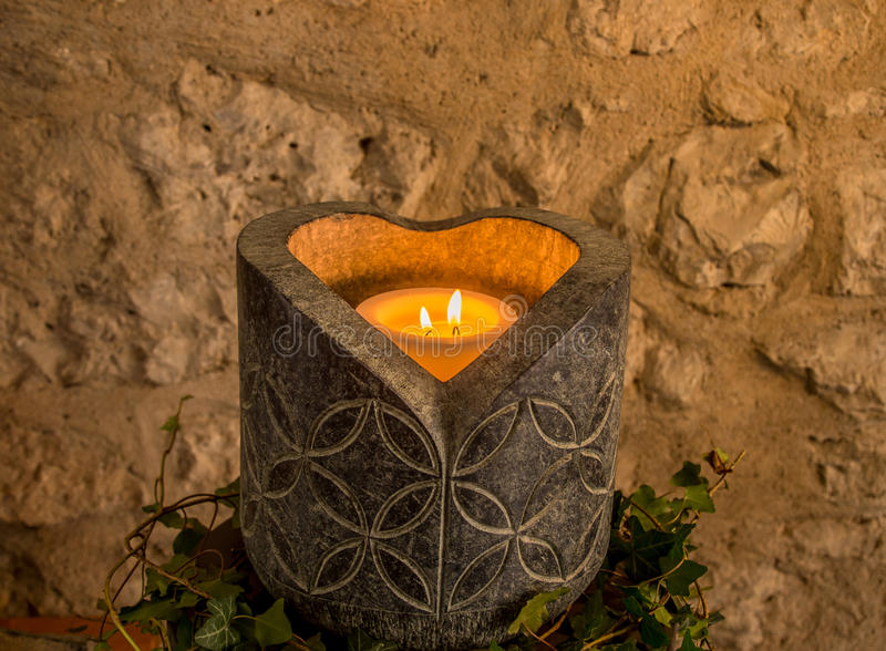 Stone candle holder. Image with a big stoned candle holder, artistic engraved and a heart shaped candle light royalty free stock photo