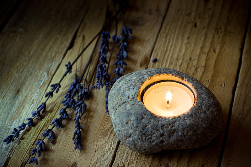 Stone candle holder with tea light on barn wood, lavender twigs, Easter, tranquility stock photo