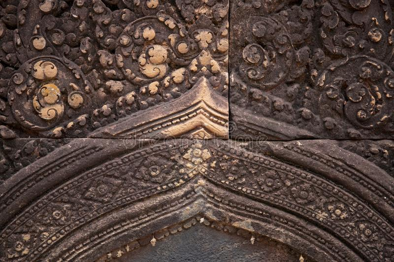 Stone carved bas-relief of Banteay Srei temple in Angkor Wat, Cambodia. Floral ornament bas-relief on cambodian temple. Khmer architecture heritage closeup royalty free stock image