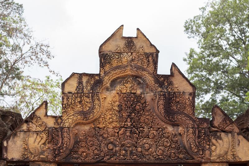 Stone carved bas-relief of Banteay Srei temple in Angkor Wat, Cambodia. Roof portal with floral ornament bas-relief. royalty free stock image