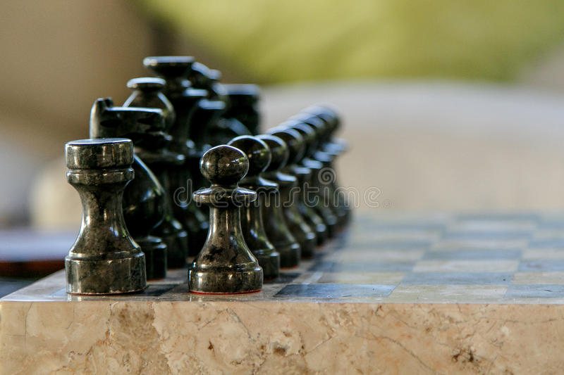 Stone carved chess pieces. On chessboard royalty free stock photography