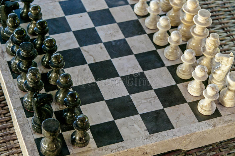 Stone carved chess pieces. On chessboard stock image