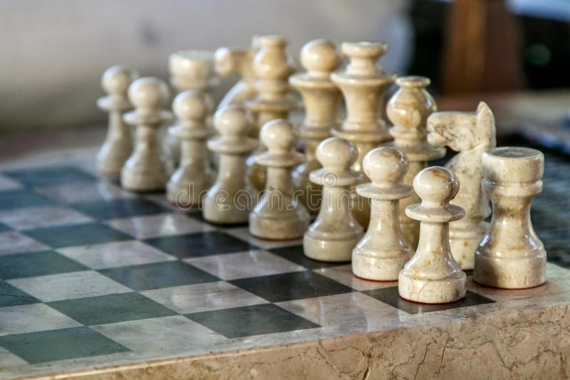 Stone carved chess pieces. On chessboard. Shallow DOF, focus on front pieces royalty free stock photo