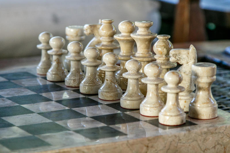 Stone carved chess pieces. On chessboard. Shallow DOF, focus on pieces in the middle royalty free stock image