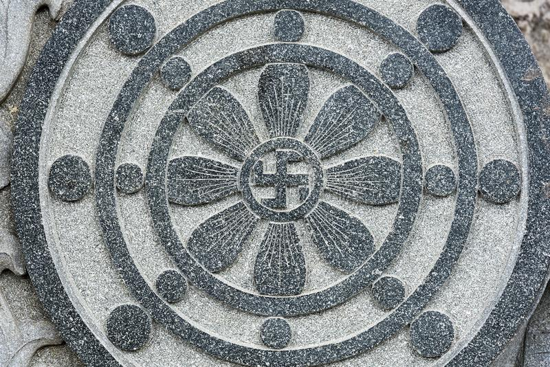 Stone carved radial design with Buddhist swastika symbol at the centre stock photos