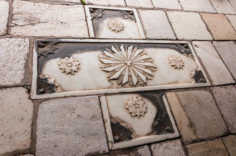 Stone carving art example, abstract christian cross decor element on pavement, walkway in Old Town of Skopje, Macedonia stock images