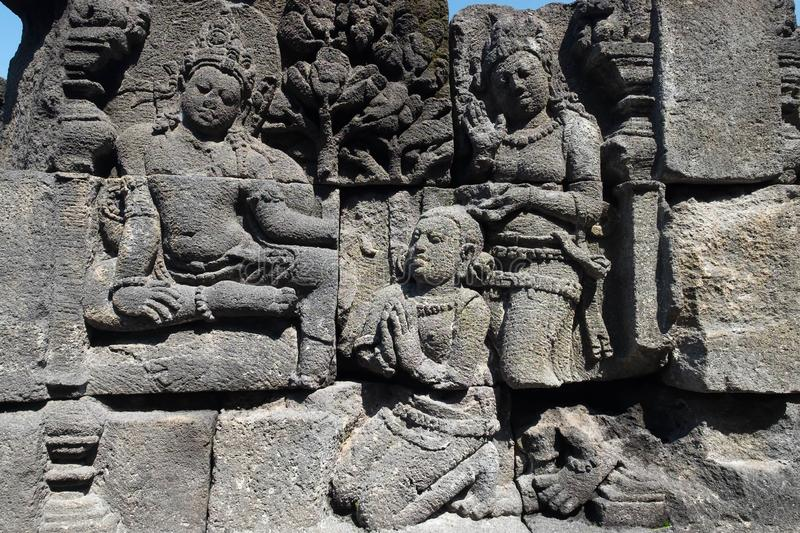 Stone carving. at Borobudur temple, Magelang, Indonesia. Closeup wall ornamented with bas-reliefs religion scene. Highly detailed stone carving. Borobudur royalty free stock images