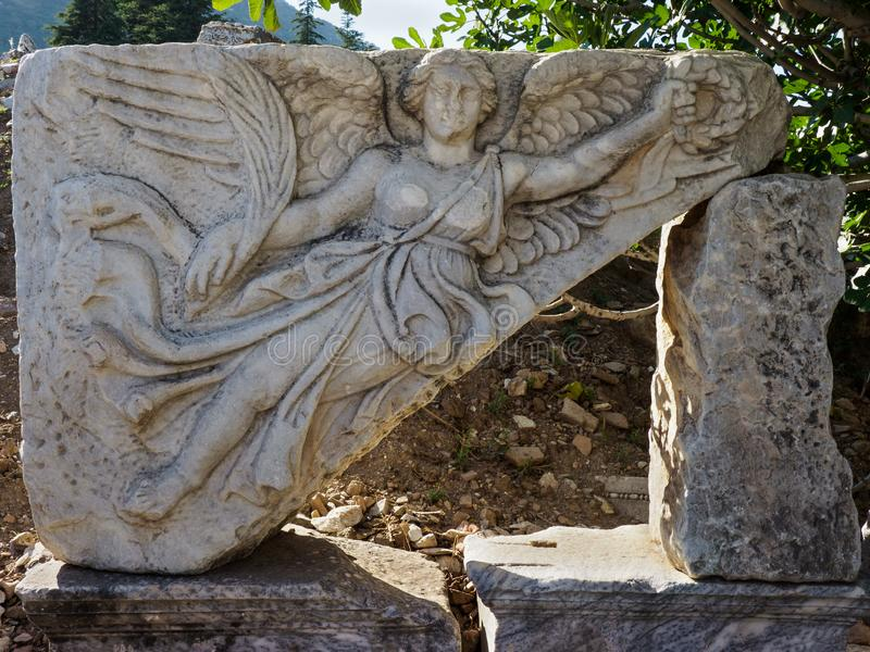 Stone carving of the goddess Nike at the ruins of the ancient city of Ephesus, Turkey. Stone carving of the goddess Nike at the ruins of the ancient city of stock image