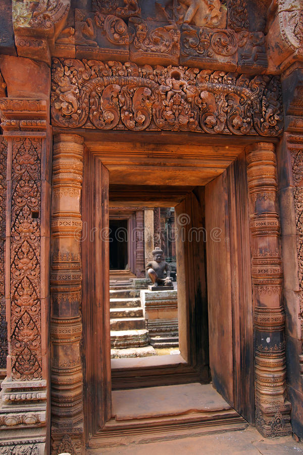 Stone carving on red sandstone doorways. Intricate stone carving on red sandstone doorways and portals, Banteay Srei, Cambodia stock images