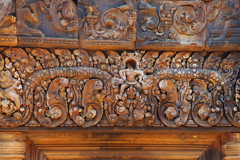 Stone carving on red sandstone doorways. Intricate stone carving on red sandstone doorways and portals, Banteay Srei, Cambodia royalty free stock photo