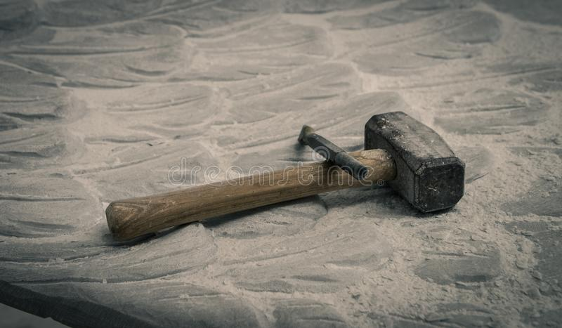 Stone carving tools on a white marble sculpture. Detail of some tools for working stone, art craft and manual on a white marble sculpture in Carrara, Tuscany stock photo