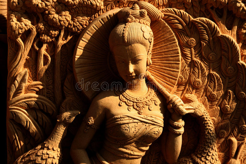 Stone carving of a woman holding an umbrella. royalty free stock image