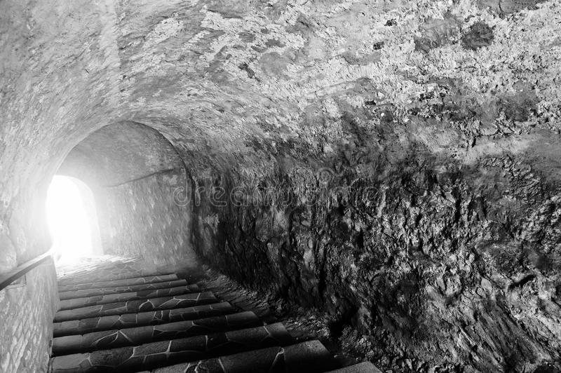 Stone cave with a light at the end of the tunnel. Scary black an stock images