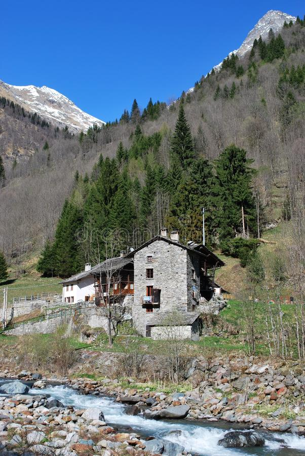 Stone chalet. Typical stone chalet on Alps moutains and Sesia river, Alagna village, Piedmont, Italy royalty free stock photo